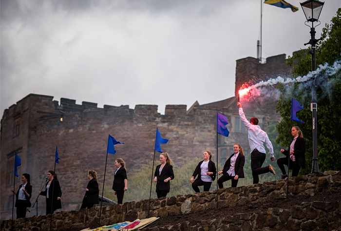 dancers with flare in front of castle